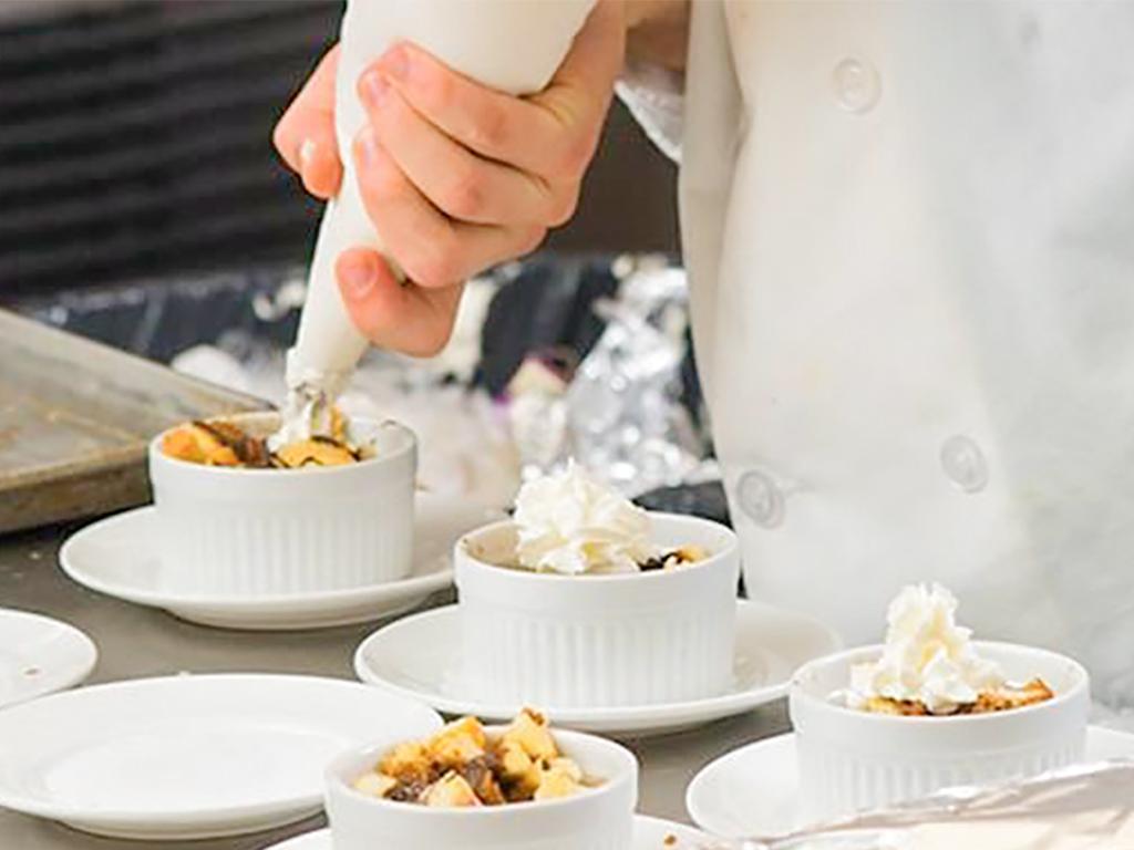 Student applying dessert piping.