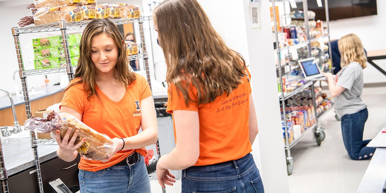 Students stocking food in shop.