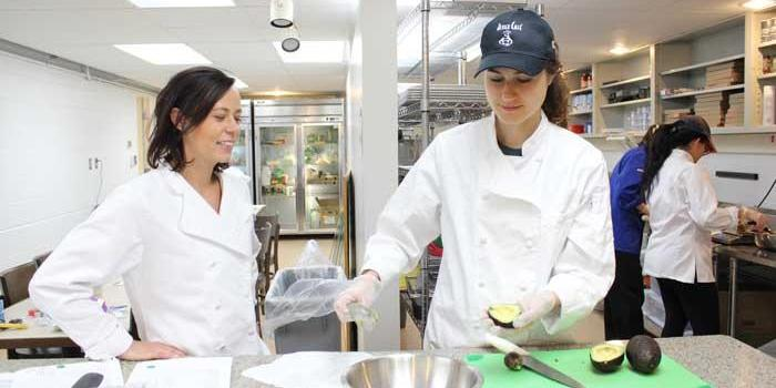 Students cut avacadoes in kitchen.