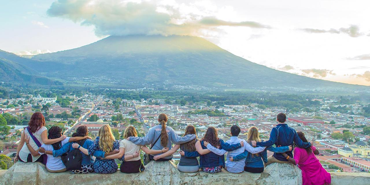 Study abroad students with their backs to the camera looking onto a town and volcano