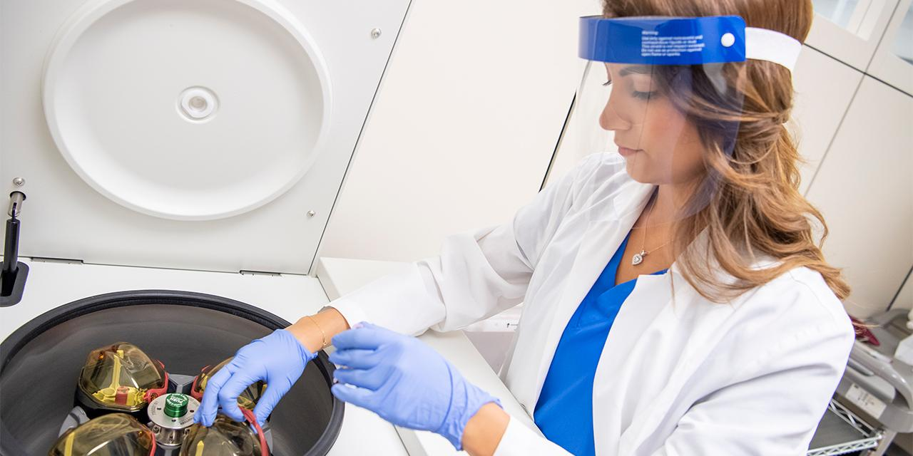 Student working in a lab with a shield over their face